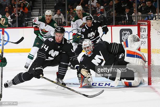 Calvin de Haan and JeanFrancois Berube of the New York Islanders defend the net during the game against the Minnesota Wild at the Barclays Center on...