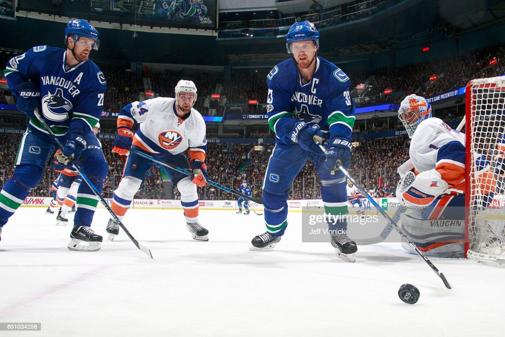 Calvin de Haan #44 and Thomas Greiss #1 of the New York Islanders and Daniel Sedin #22 and Henrik Sedin #33 of the Vancouver Canucks look at a loose puck during their NHL game at Rogers Arena March 9, 2017 in Vancouver, British Columbia, Canada. New York won 4-3 in overtime.