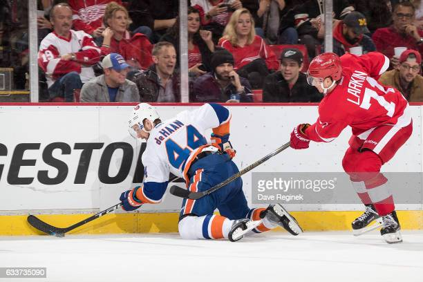 Calvin de Haan of the New York Islanders battles for the puck along the boards with Dylan Larkin of the Detroit Red Wings during an NHL game at Joe...