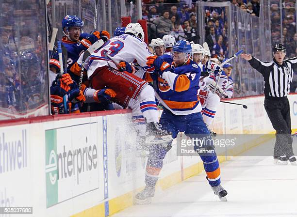 Calvin de Haan of the New York Islanders checks Jayson Megna of the New York Rangers into the Islander bench during the third period at the Barclays...