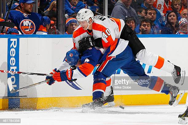 Calvin de Haan of the New York Islanders is checked by Vincent Lecavalier of the Philadelphia Flyers at Nassau Veterans Memorial Coliseum on January...