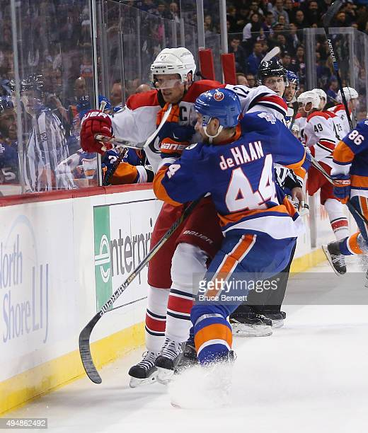 Calvin de Haan of the New York Islanders rides Eric Staal of the Carolina Hurricanes into the boards during the third period at the Barclays Center...