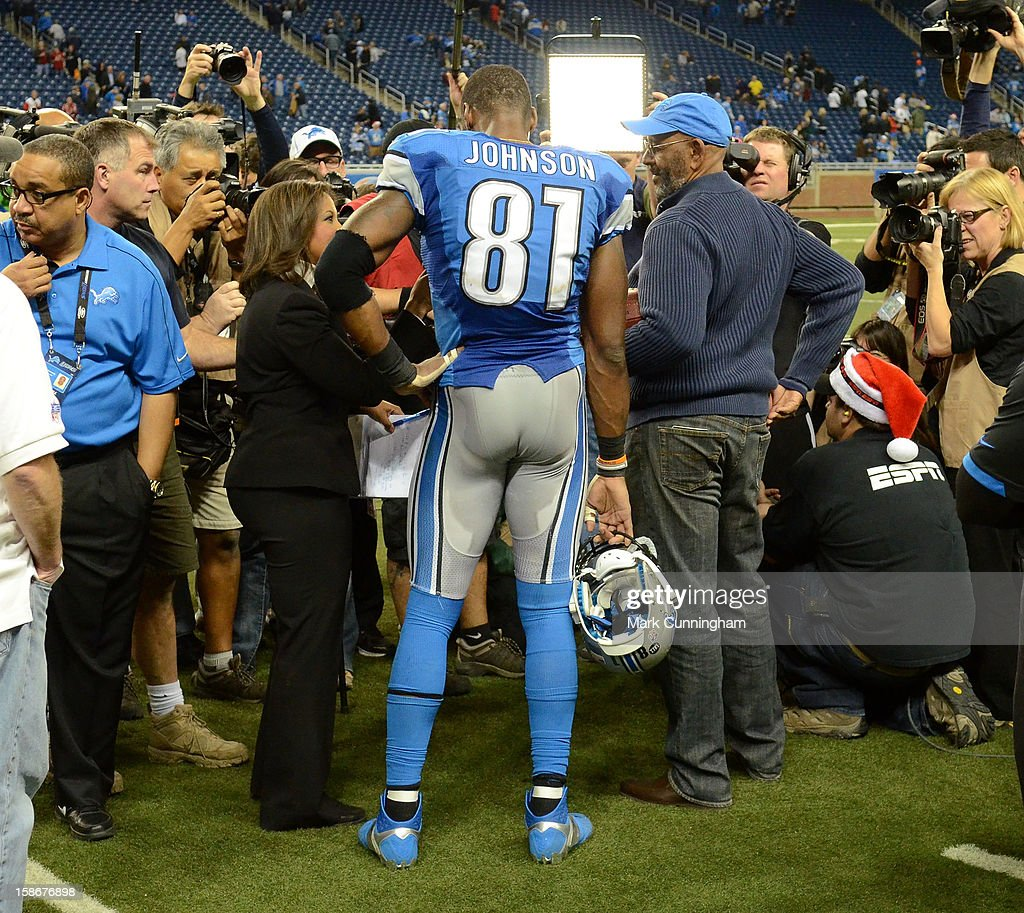 Calvin Johnson #81 of the Detroit Lions and his father Calvin Johnson Sr. talk to the media after the game against the Atlanta Falcons at Ford Field on December 22, 2012 in Detroit, Michigan. During the game Johnson broke the NFL single season yardage record formally held by Jerry Rice. The Falcons defeated the Lions 31-18.