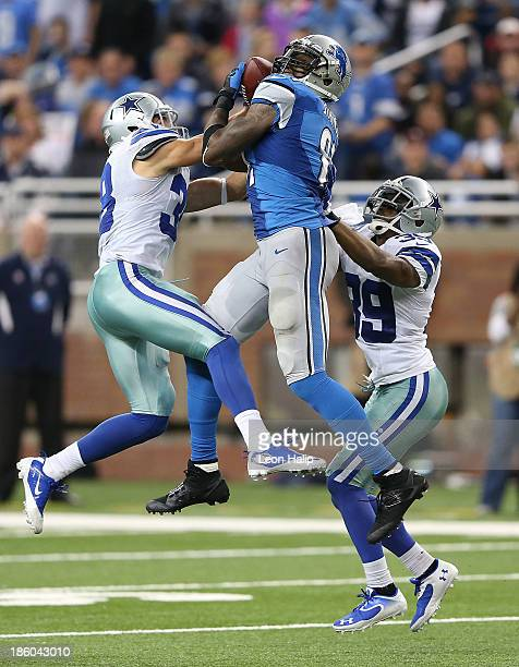 Calvin Johnson of the Detroit Lions leaps between Jeff Heath and Brandon Carr of the Dallas Cowboys and makes a 54 yard catch during the fourth...