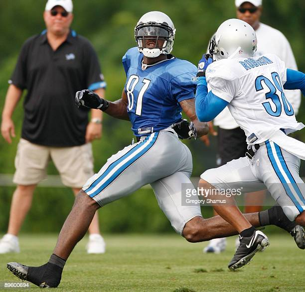 Calvin Johnson of the Detroit Lions looks for the ball behind Ramzee Robinson during training camp at the Detroit Lions Headquarters and Training...