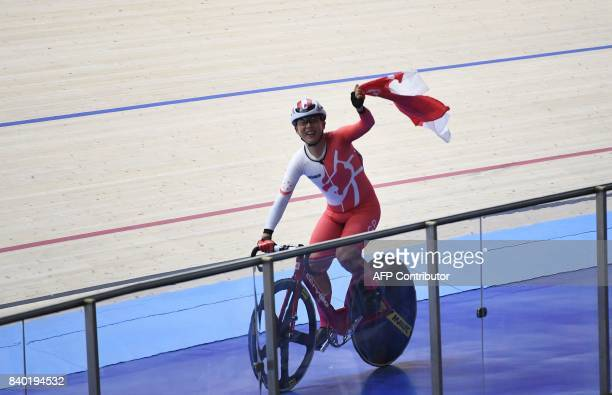 Calvin Sim of Singapore holds Singapore's flag after winning the men's omnion cycling at the 29th Southeast Asian Games in Nilai on August 28 2017 /...