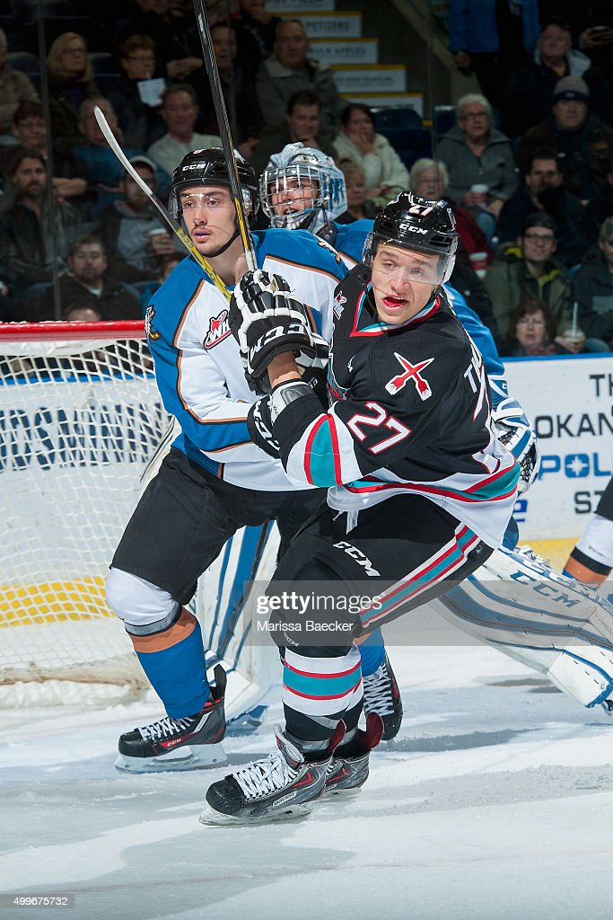 Calvin Thurkauf #27 of Kelowna Rockets is checked by a player of the Kootenay Ice during first period on December 2, 2015 at Prospera Place in Kelowna, British Columbia, Canada.