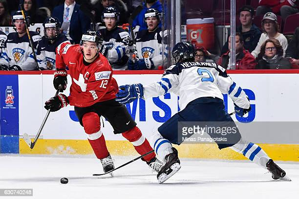 Calvin Thurkauf of Team Switzerland skates the puck against Miro Heiskanen of Team Finland during the 2017 IIHF World Junior Championship preliminary...