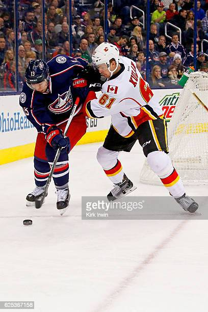 Cam Atkinson of the Columbus Blue Jackets and Brett Kulak of the Calgary Flames battle for control of the puck during the second period on November...