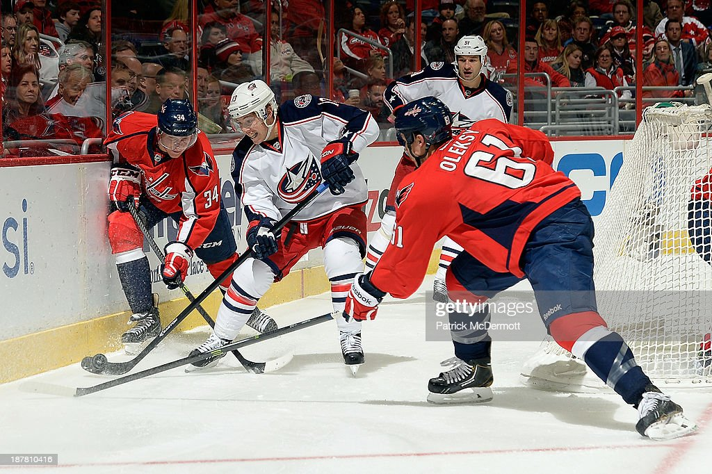 <a gi-track='captionPersonalityLinkClicked' href=/galleries/search?phrase=Cam+Atkinson&family=editorial&specificpeople=6270272 ng-click='$event.stopPropagation()'>Cam Atkinson</a> #13 of the Columbus Blue Jackets battles for the puck against <a gi-track='captionPersonalityLinkClicked' href=/galleries/search?phrase=Alexander+Urbom&family=editorial&specificpeople=6254340 ng-click='$event.stopPropagation()'>Alexander Urbom</a> #34 and Steve Oleksy #61 of the Washington Capitals in the third period during an NHL game at Verizon Center on November 12, 2013 in Washington, DC.