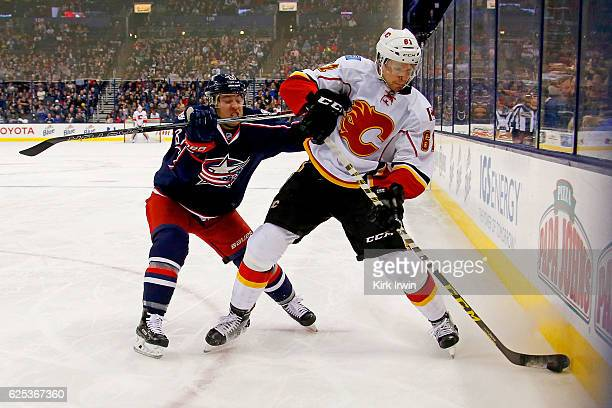 Cam Atkinson of the Columbus Blue Jackets checks Brett Kulak of the Calgary Flames while battling for control of the puck during the first period on...