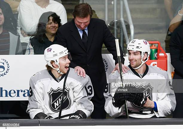 Cam Atkinson of the Columbus Blue Jackets coach Wayne Gretzky and John Tavares of the New York Islanders share a laugh on the bench during the...