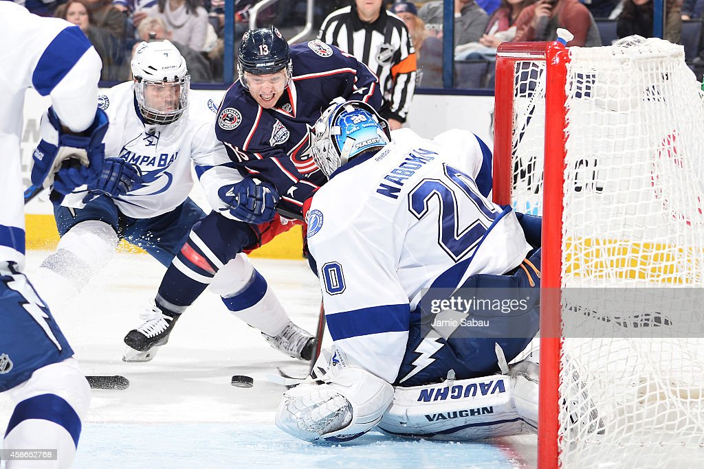 Cam Atkinson of the Columbus Blue Jackets drives to the net and puts a shot on goaltender Evgeni Nabokov of the Tampa Bay Lightning as Radko Gudas of...