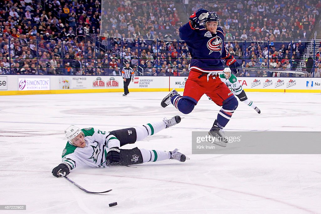 Cam Atkinson of the Columbus Blue Jackets leaps over Kevin Connauton of the Dallas Stars while chasing after the puck during the second period on...