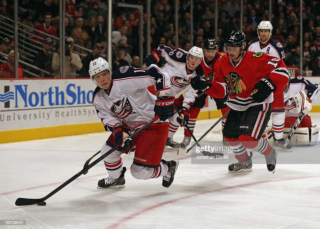 Cam Atkinson of the Columbus Blue Jackets looks to pass as Marcus Kruger of the Chicago Blackhawks closes in at the United Center on March 1 2013 in...