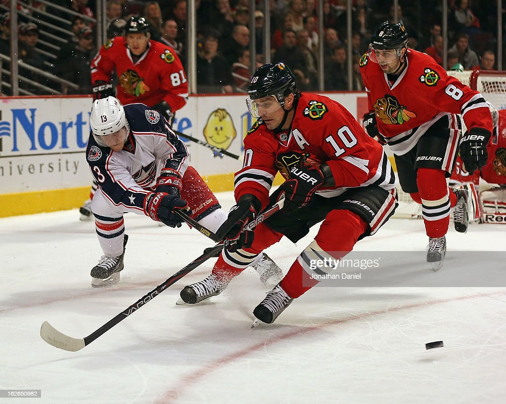 Cam Atkinson #13 of the Columbus Blue Jackets passes the puck around Patrick Sharp #10 of the Chicago Blackhawks at the United Center on February 24, 2013 in Chicago, Illinois. The Blackhawks defeated the Blue Jackets 1-0.
