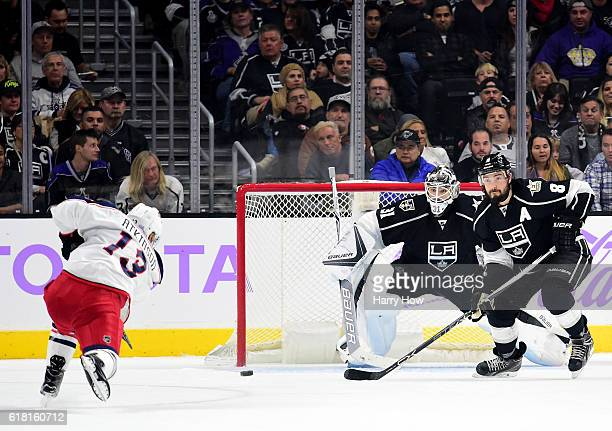 Cam Atkinson of the Columbus Blue Jackets scores on a powerplay past Peter Budaj and Drew Doughty of the Los Angeles Kings to take a 21 lead during...