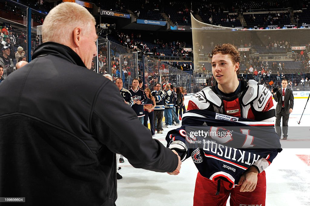 Cam Atkinson #13 of the Columbus Blue Jackets shakes hands and gives his jersey to a fan after the game against the Detroit Red Wings on January 21, 2013 at Nationwide Arena in Columbus, Ohio. Detroit defeated Columbus 4-3 in a shootout.