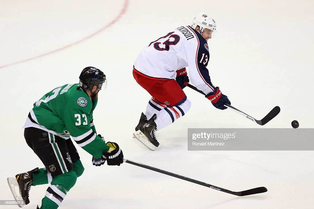 <a gi-track='captionPersonalityLinkClicked' href=/galleries/search?phrase=Cam+Atkinson&family=editorial&specificpeople=6270272 ng-click='$event.stopPropagation()'>Cam Atkinson</a> #13 of the Columbus Blue Jackets skates the puck against <a gi-track='captionPersonalityLinkClicked' href=/galleries/search?phrase=Alex+Goligoski&family=editorial&specificpeople=791866 ng-click='$event.stopPropagation()'>Alex Goligoski</a> #33 of the Dallas Stars in the third period at American Airlines Center on April 9, 2014 in Dallas, Texas.
