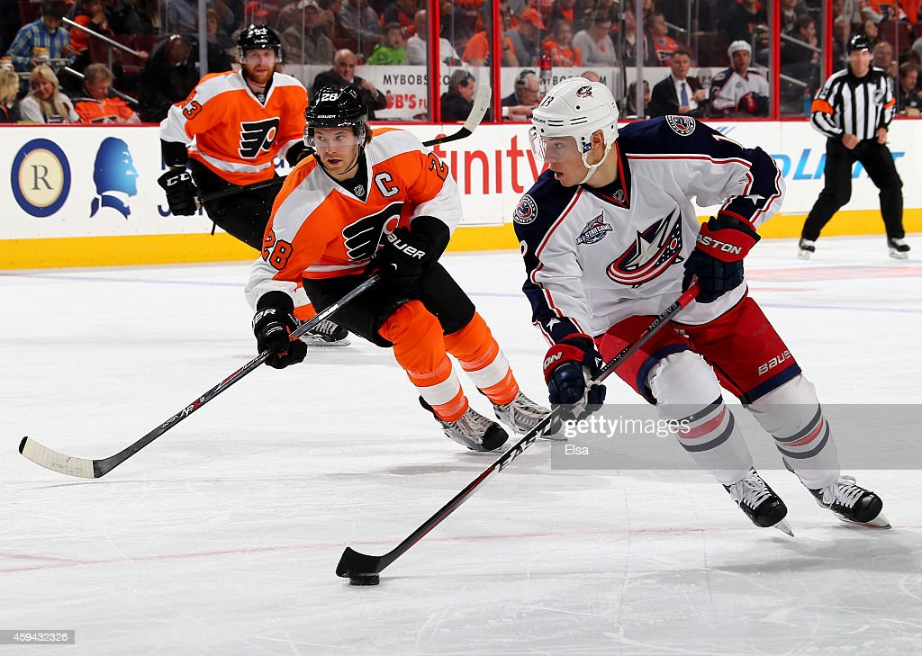 Cam Atkinson #13 of the Columbus Blue Jackets takes the puck as Claude Giroux #28 of the Philadelphia Flyers defends on November 22, 2014 at the Wells Fargo Center in Philadelphia, Pennsylvania.