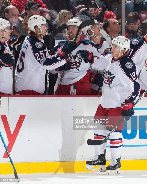Cam Atkinson of the Columbus Blue Jackets taps gloves with teammates on the bench after scoring a goal during an NHL game against the Detroit Red...