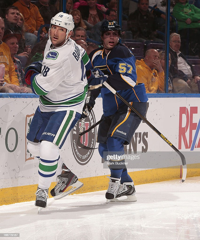 Cam Barker #18 of the Vancouver Canucks skates against <a gi-track='captionPersonalityLinkClicked' href=/galleries/search?phrase=David+Perron&family=editorial&specificpeople=4282591 ng-click='$event.stopPropagation()'>David Perron</a> #57 of the St. Louis Blues in an NHL game on April 16, 2013 at Scottrade Center in St. Louis, Missouri.
