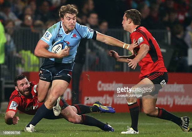 Cam Crawford of the Waratahs runs with the ball in defender Tom Taylor of the Crusaders with team mate Ryan Crotty diving in behind during the round...