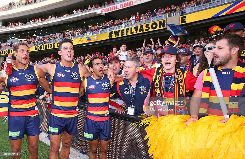 Cam EllisYolmen Taylor Walker and Eddie Betts of the Crows sing the club song with fans during the round one AFL match between the Adelaide Crows and...