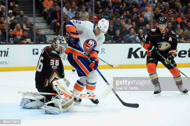 Cam Fowler and John Gibson of the Anaheim Ducks defend against a shot deflected by Anders Lee of the New York Islanders during the second period of a...