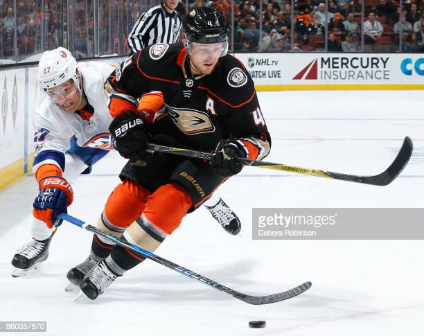 Cam Fowler of the Anaheim Ducks battles for the puck against Anders Lee of the New York Islanders during the game on October 11 2017 at Honda Center...