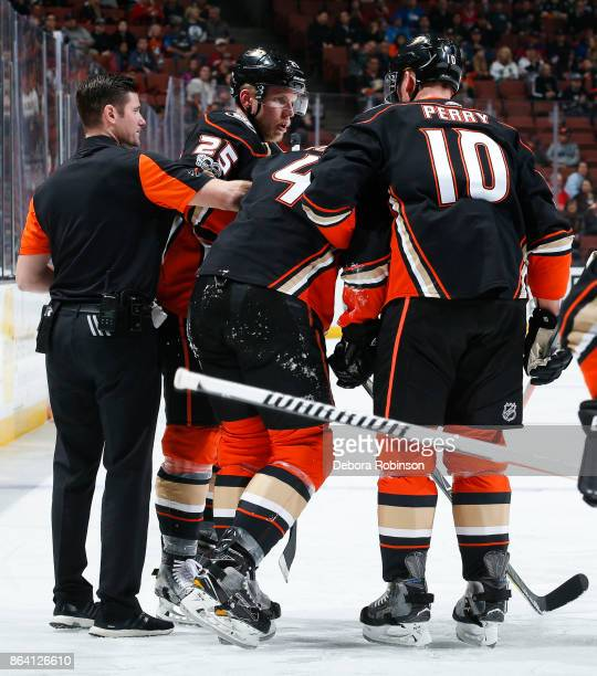 Cam Fowler of the Anaheim Ducks is helped off the ice by Ondrej Kase and Corey Perry after being injured when an opponent's stick became lodged in...