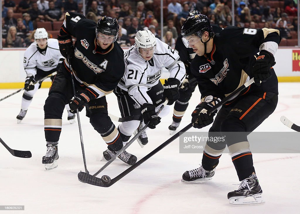 <a gi-track='captionPersonalityLinkClicked' href=/galleries/search?phrase=Cam+Fowler&family=editorial&specificpeople=5484080 ng-click='$event.stopPropagation()'>Cam Fowler</a> #4 of the Anaheim Ducks, <a gi-track='captionPersonalityLinkClicked' href=/galleries/search?phrase=Matt+Frattin&family=editorial&specificpeople=5648435 ng-click='$event.stopPropagation()'>Matt Frattin</a> #21 of the Los Angeles Kings and <a gi-track='captionPersonalityLinkClicked' href=/galleries/search?phrase=Ben+Lovejoy&family=editorial&specificpeople=4509565 ng-click='$event.stopPropagation()'>Ben Lovejoy</a> #6 of the Ducks fight for the puck in the second period at Honda Center on September 17, 2013 in Anaheim, California. The Kings defeated the Ducks 6-0.