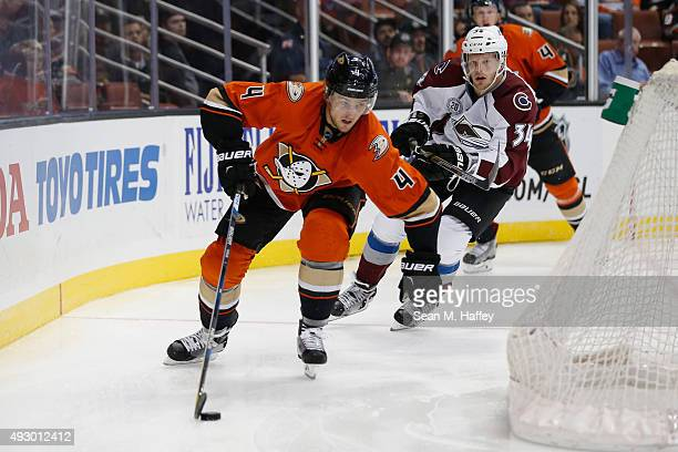 Cam Fowler of the Anaheim Ducks skates with the puck as Carl Soderberg of the Colorado Avalanche pursues him during the first period of a game at...