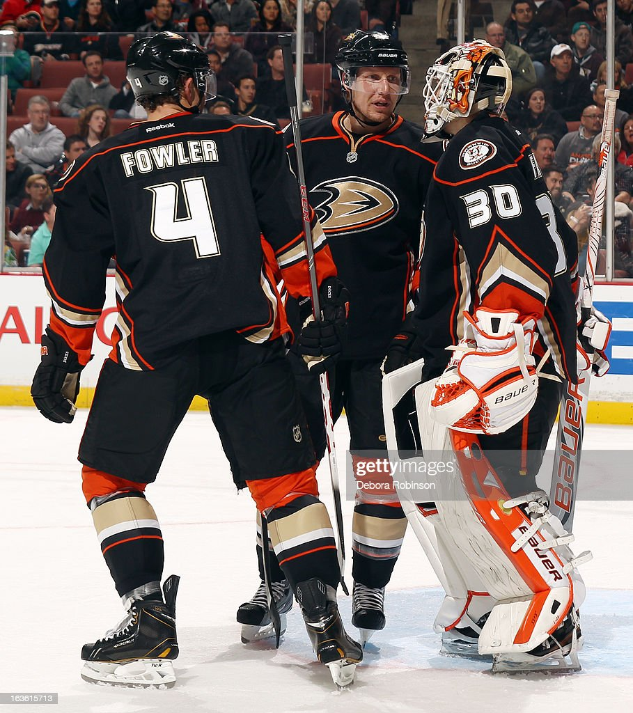 Cam Fowler #4, Toni Lydman #32 and Viktor Fasth #30 of the Anaheim Ducks talk during the game against the Calgary Flames on March 8, 2013 at Honda Center in Anaheim, California.