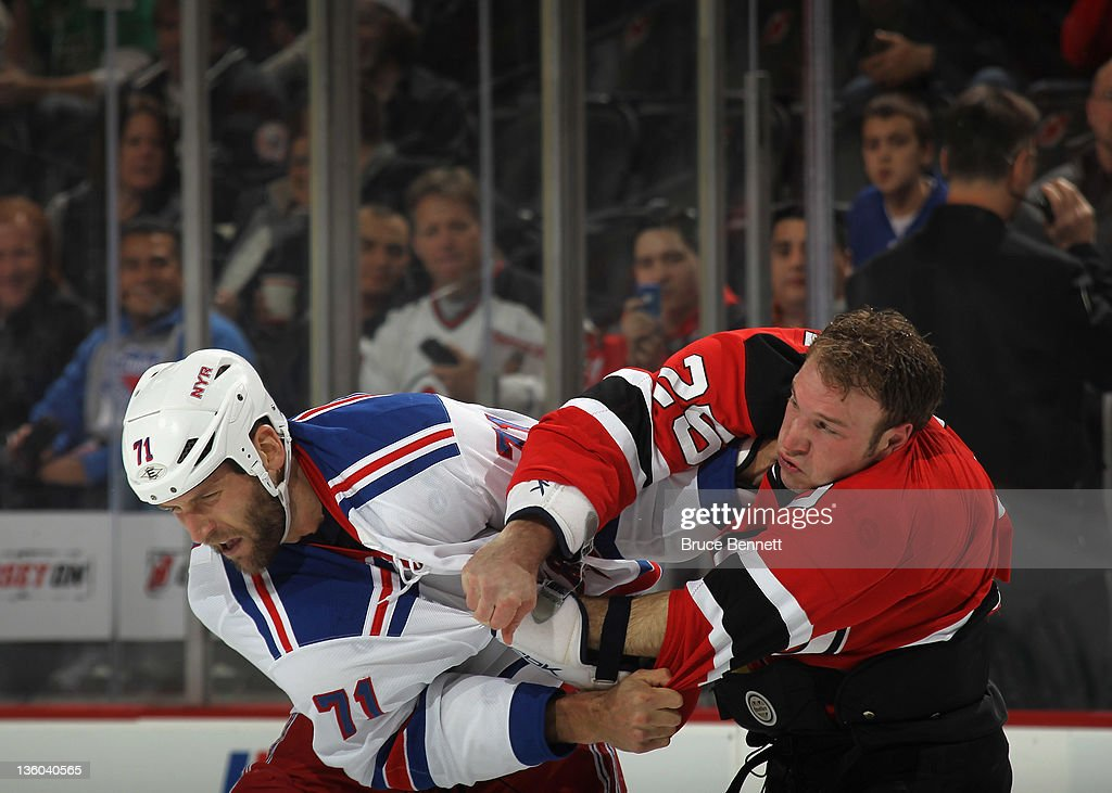 <a gi-track='captionPersonalityLinkClicked' href=/galleries/search?phrase=Cam+Janssen&family=editorial&specificpeople=570570 ng-click='$event.stopPropagation()'>Cam Janssen</a> #25 of the New Jersey Devils and Mike Rupp #71 of the New York Rangers fight just three seconds into the first period at the Prudential Center on December 20, 2011 in Newark, New Jersey.