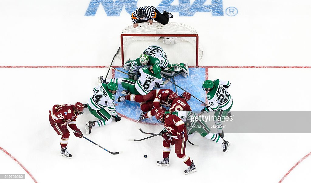 Cam Johnson #33 of North Dakota Fighting Hawks is surrounded by his teammates in the crease including Troy Stecher #2, Rhett Gardner #22, Paul LaDue #6 and Austin Poganski #14 as well as a few Denver Pioneers including Dylan Gambrell #7, Trevor Moore #8, Danton Heinen 320 and Troy Terry #19 during game two of the 2016 NCAA Division I Men's Hockey Frozen Four Championship Semifinal at the Amaile Arena on April 7, 2016 in Tampa, Florida. The Fighting Hawks won 4-2.
