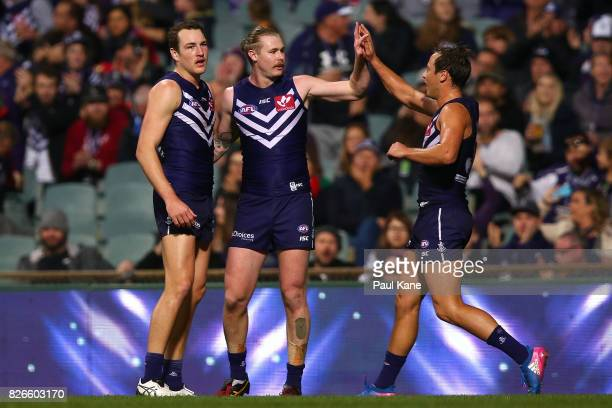 Cam McCarthy of the Dockers celebrates a goal with Brennan Cox and Cameron Sutcliffe during the round 20 AFL match between the Fremantle Dockers and...