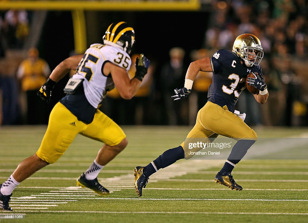 <a gi-track='captionPersonalityLinkClicked' href=/galleries/search?phrase=Cam+McDaniel&family=editorial&specificpeople=9937391 ng-click='$event.stopPropagation()'>Cam McDaniel</a> #33 of the Notre Dame Fighting Irish is chased by Joe Bolden #35 of the Michigan Wolverines at Notre Dame Stadium on September 6, 2014 in South Bend, Indiana.