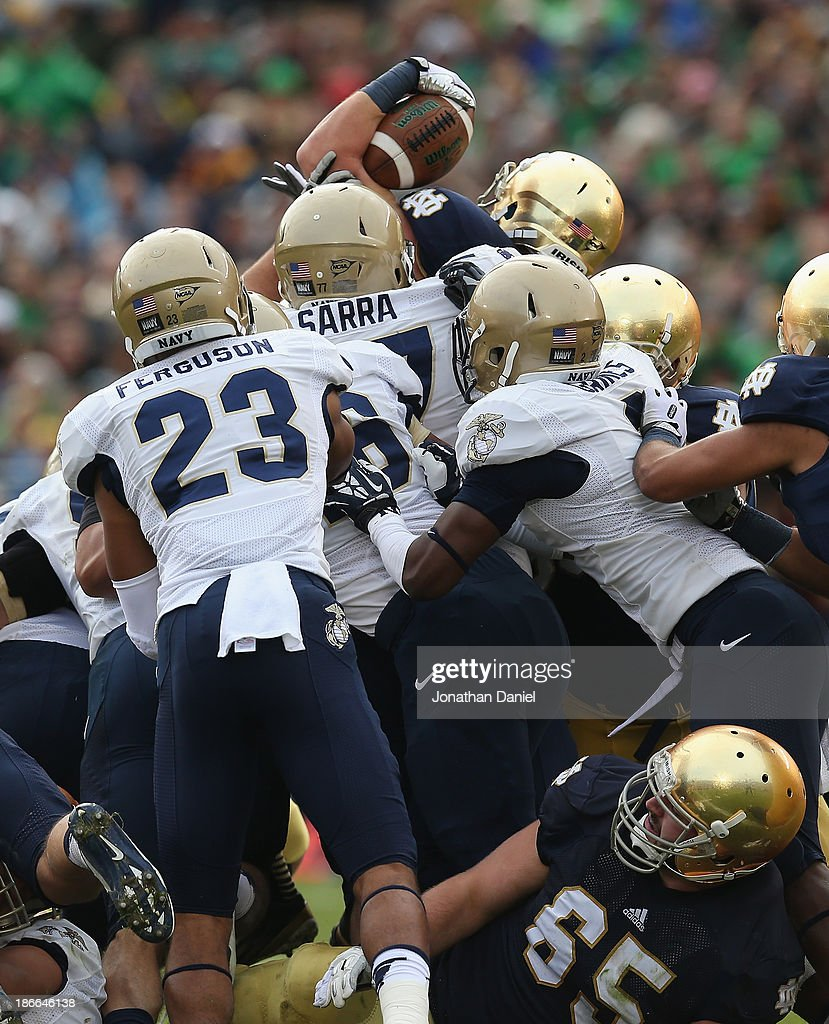 Cam McDaniel of the Notre Dame Fighting Irish leaps over a pile of tacklers including Bernard Sarra and Chris Ferguson of the Navy Midshipmen to get...