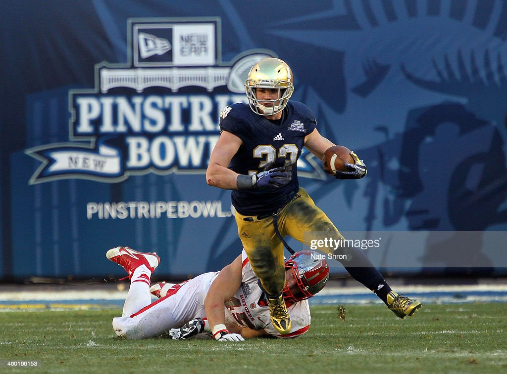 <a gi-track='captionPersonalityLinkClicked' href=/galleries/search?phrase=Cam+McDaniel&family=editorial&specificpeople=9937391 ng-click='$event.stopPropagation()'>Cam McDaniel</a> #33 of the Notre Dame Fighting Irish runs the ball against Kevin Snyder #45 of the Rutgers Scarlet Knights during the New Era Pinstripe Bowl at Yankee Stadium on December 28, 2013 in the Bronx Borough of New York City.