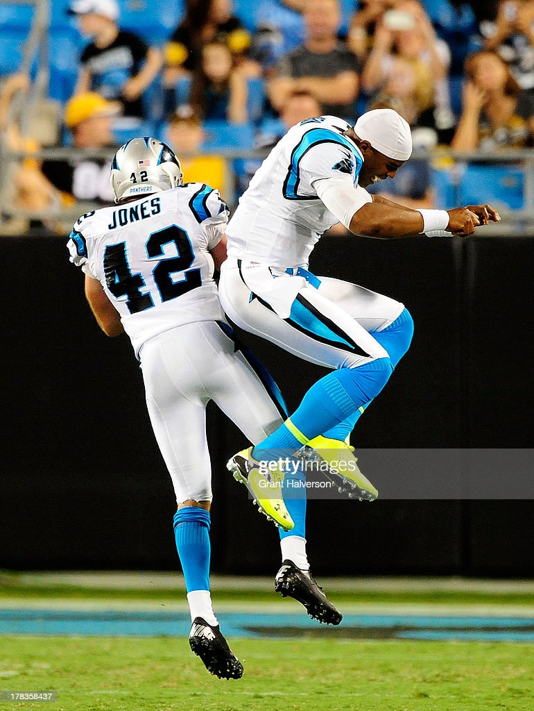 Cam Newton #1 and Colin Jones #42 of the Carolina Panthers celebrate after Jones' second interception of Pittsburgh Steelers quarterback Landry Jones during a preseason NFL game at Bank of America Stadium on August 29, 2013 in Charlotte, North Carolina. The Panthers won 25-10.