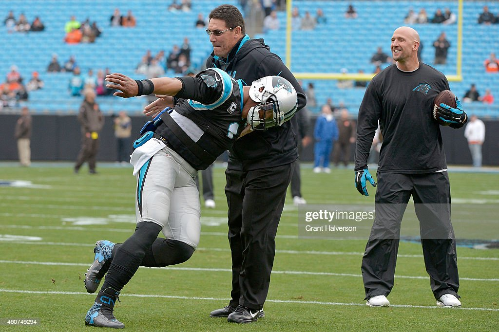 Cam Newton jokes with head coach Ron Rivera of the Carolina Panthers as he warms up before their game against the Cleveland Browns at Bank of America...