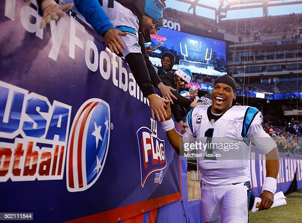 Cam Newton of the Carolina Panthers celebrates with fans after defeating the New York Giants in their game at MetLife Stadium on December 20 2015 in...