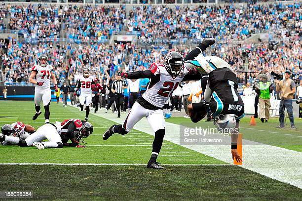 Cam Newton of the Carolina Panthers dives into the end zone for a touchdown in front of defender Christopher Owens f the Atlanta Falcons during play...