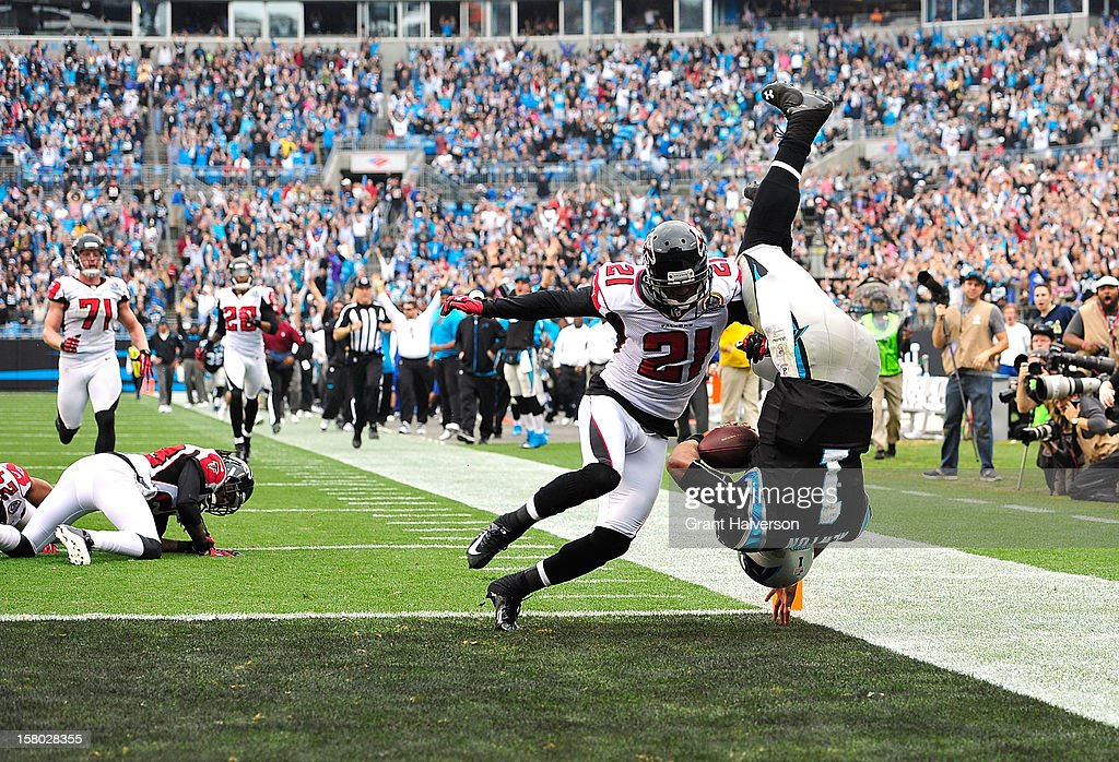 Cam Newton #1 of the Carolina Panthers dives into the end zone for a touchdown in front of defender Christopher Owens #21 f the Atlanta Falcons during play at Bank of America Stadium on December 9, 2012 in Charlotte, North Carolina.