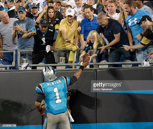 Cam Newton of the Carolina Panthers gives a fan a ball after a 3rd quarter touchdown against the Pittsburgh Steelers during their game at Bank of...