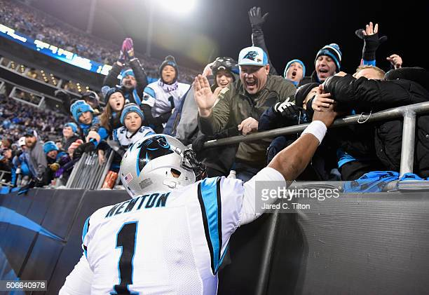 Cam Newton of the Carolina Panthers gives a game ball to a fan after Corey Brown scored an 86 yard touchdown in the first quarter against the Arizona...