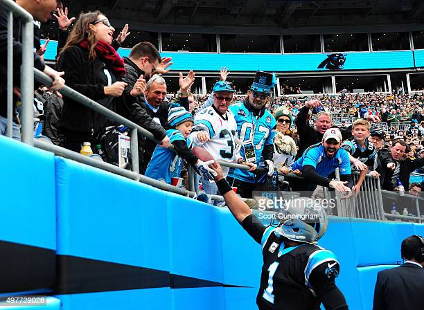 Cam Newton of the Carolina Panthers hands the football to a young fan after scoring a touchdown against the Green Bay Packers at Bank Of America...