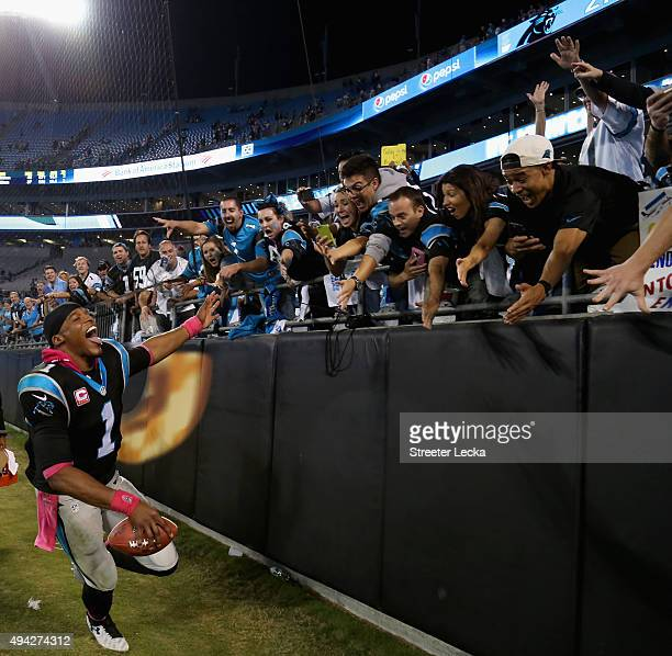 Cam Newton of the Carolina Panthers high fives fans after defeating the Philadelphia Eagles at Bank of America Stadium on October 25 2015 in...