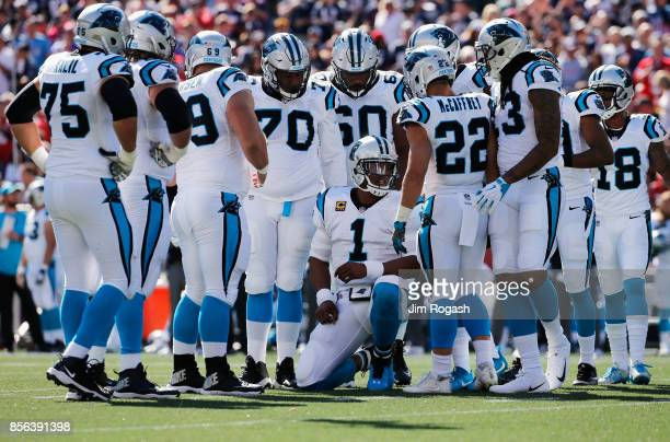Cam Newton of the Carolina Panthers huddles with teammates during the first half against the New England Patriots at Gillette Stadium on October 1...